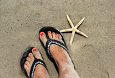 Beautiful female feet on the beach and starfish — Stock Photo