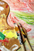 Art palette, paintbrushes and picture with flowers — Foto Stock
