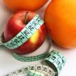 Stock Photo: Fruits and measurement tape on white background