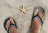 Beautiful female feet on the beach — Fotografia Stock