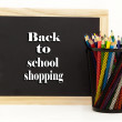 Back To School Shopping Chalkboard With Colored Pencils — Stock Photo