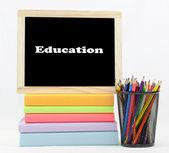 образование текст доске на цветные книги с цветными карандашами — Стоковое фото