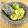 Stock Photo: Molcajete Mortar And Pestle Bowl Filled With Guacamole And Lim