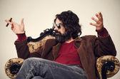 Man sitting in an armchair smoking cigar and having a conversati — Stock Photo