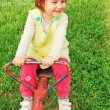Happy little girl swinging on see-saw — Stock Photo