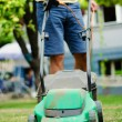 Stock Photo: Man moves with lawnmower & mows green grass