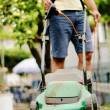 Man moves with lawnmower & mows green grass — Stock Photo