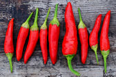 Red chili peppers on an old wooden background — Stock Photo