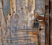 Old wooden door with rusty latch and padlock — Stock Photo