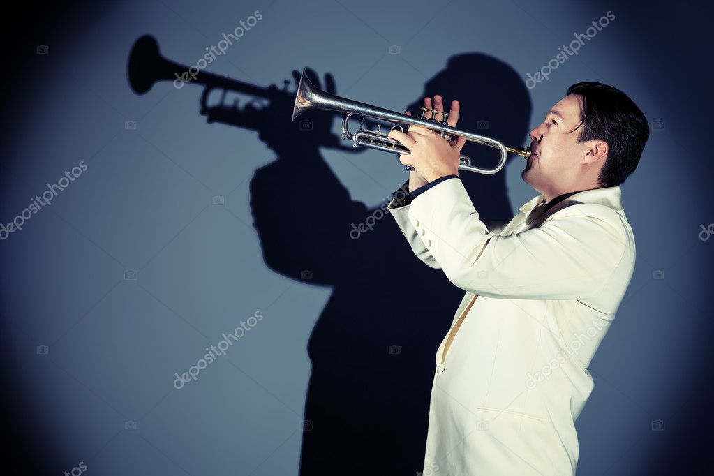Portrait of a musician playing the trumpet at studio.   Stock Photo #12482440