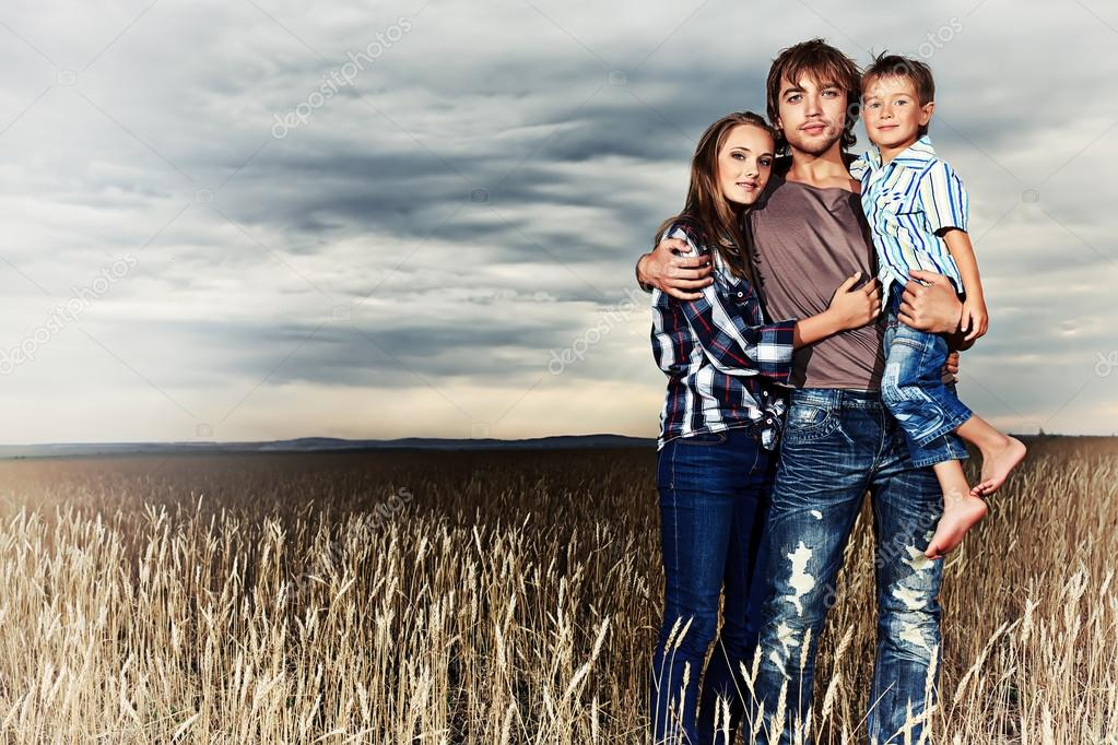 Happy family standing together in the wheat field over beautiful cloudy sky.   Stock Photo #12482499