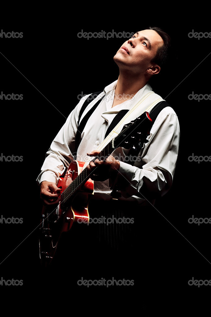 Portrait of a professional artist playing on guitar. Over black background. — Stock Photo #12600749