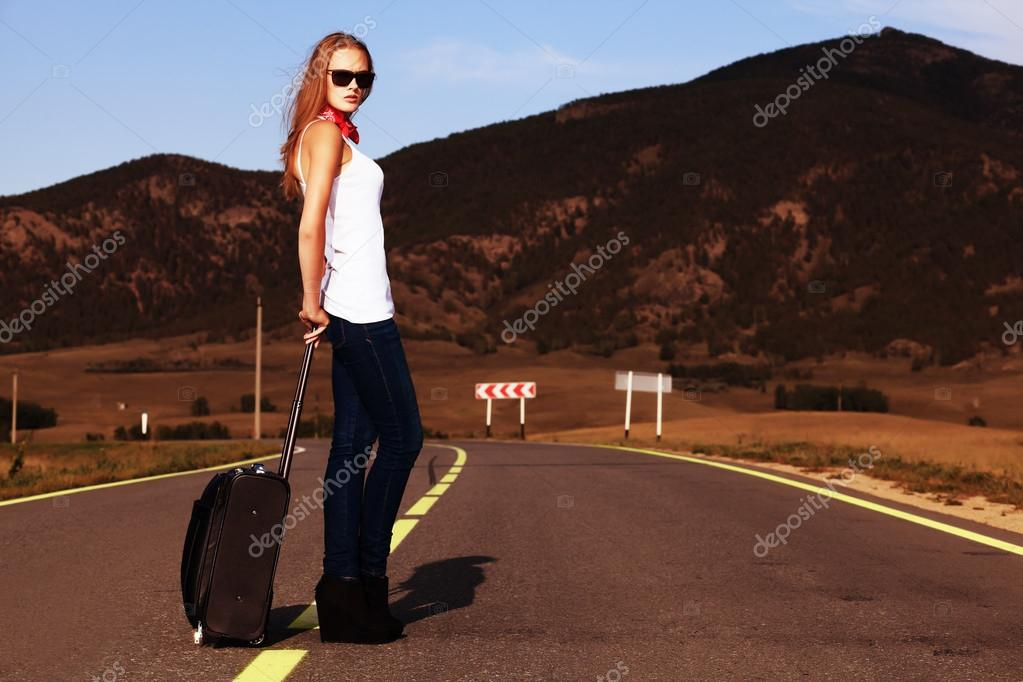 Attractive young woman hitchhiking along a road. — Stock Photo #12737311