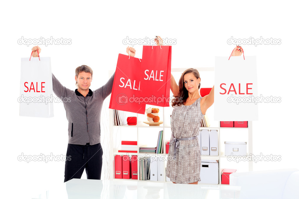 Seasonal sale: happy couple holding shopping bags inside of a store. — Stock Photo #12737343