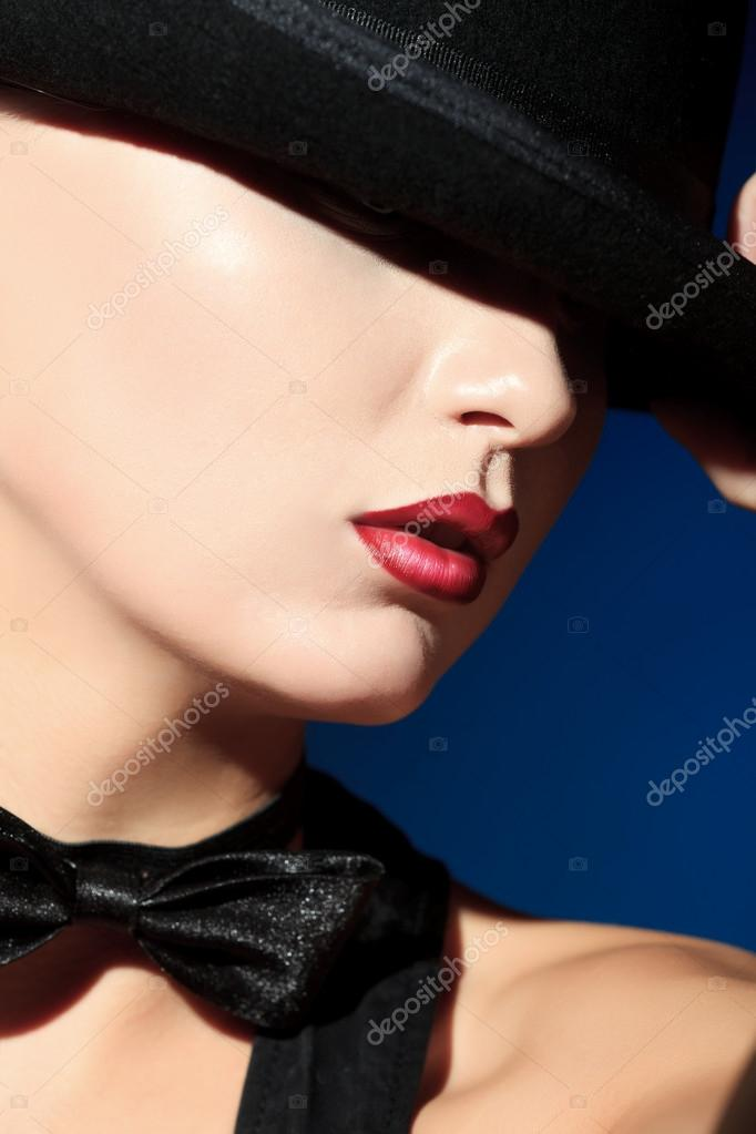Portrait of the elegant young woman posing in black pot hat. Light and shadow.  Stock Photo #12797650