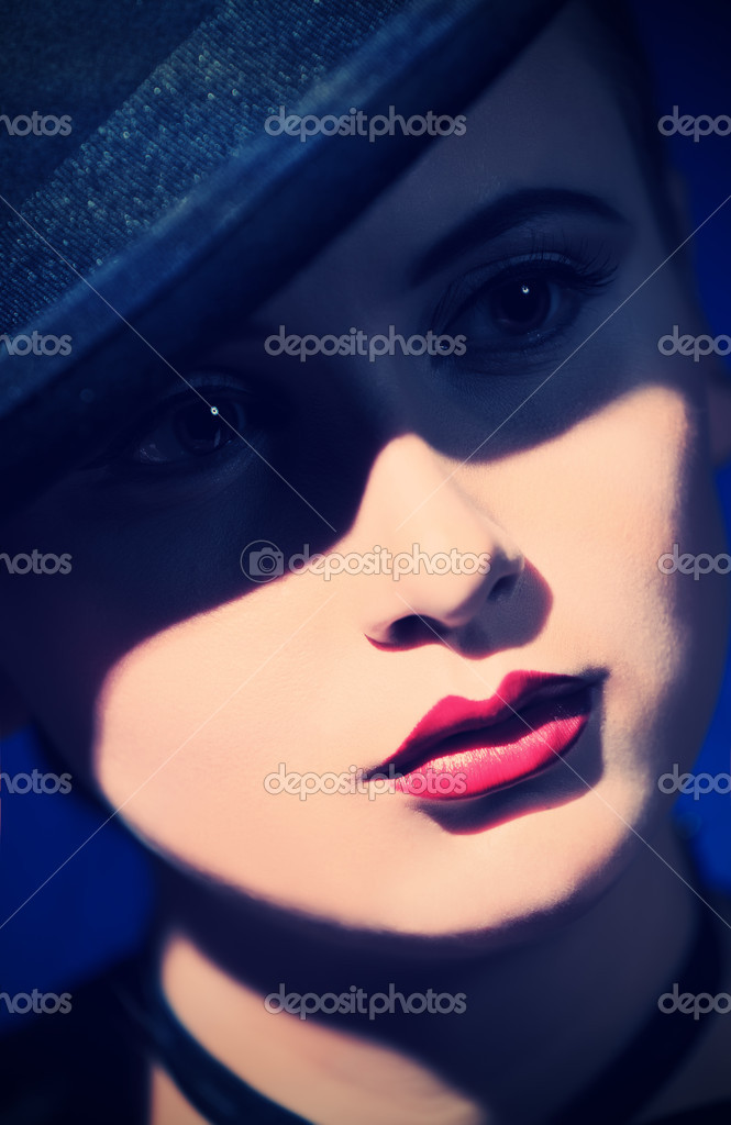 Portrait of the elegant young woman posing in black pot hat. Light and shadow. — Stock Photo #12797742