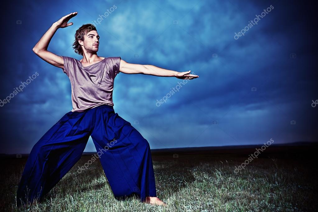 Fashionable male model posing in the field over stormy evening sky. — Stock Photo #13563601