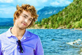Happy young man standing over sea and blue sky. — Stock Photo