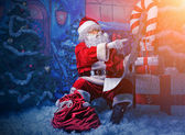 Santa Claus posing with a list of presents over Christmas background. — Stock Photo