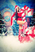Beautiful young woman in Santa Claus clothes over Christmas background. — Stock Photo