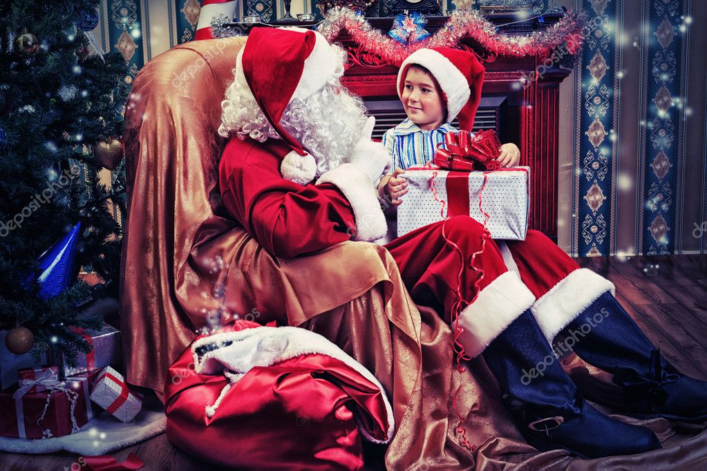 Santa Claus giving a present to a little cute boy near the fireplace and Christmas tree at home.  Stock Photo #14840133