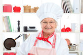 Portrait of a senior woman chef cook in the kitchen. — Stock Photo