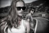 Casal de jovens modernos posando em uma estrada pitoresca paisagem. — Fotografia Stock