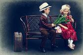 Cute little boy is giving bouquet of tulips to the charming little lady. Retro style. — Stock Photo