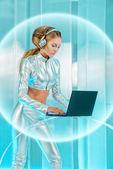 Mooie jonge vrouw in zilveren latex kostuum met futuristische kapsel en make-up werken op een laptop. sci-fi stijl. — Stockfoto