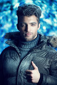 Portrait of a handsome man dressed in winter clothes, covered with frost. — Stock Photo