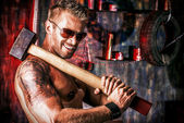 Handsome muscular man with sledgehammer working in the old garage. — Stock Photo