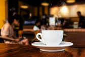 Cup of coffee on table in cafe — Stockfoto