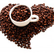 White cup with roasted coffee beans in the shape of the heart is — Stock Photo #35263133