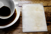 Cup of coffee with grunge notepad on wooden background — Photo