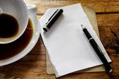 Cup of coffee with grunge notepad and pen on wooden background — Foto de Stock
