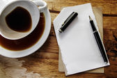 Cup of coffee with grunge notepad and pen on wooden background — Stock fotografie