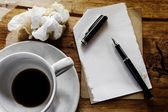 Cup of coffee with notepad, pen and crumpled paper on wooden bac — Stock fotografie