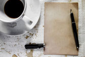 Cup of coffee with grunge notepad and pen on white tablecloth ba — Stock fotografie