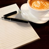 Coffee cup, spiral notebook and pen on the wooden table backgrou — Stock Photo