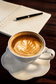 Coffee cup, spiral notebook and pen on the wooden table backgrou — Foto de Stock
