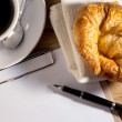 Blank white notebook,pen,cup of coffee and croissant on the de — Stock Photo