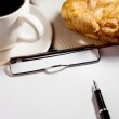 Blank white notebook,pen,cup of coffee and croissant on the de — Stock Photo #37979207
