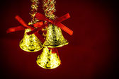 Festive bells with Christmas holly on red background — Stock Photo