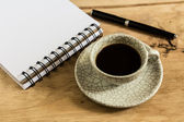 Work desk with paper, pen and cup of instant coffee — Stock Photo