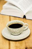 Tasse de café et ouvert de livre sur la table en bois — Photo