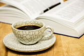 Cup of coffee and opened book with pen on wood table — Stok fotoğraf