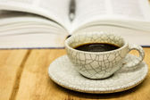 Cup of coffee and opened book with pen on wood table — Stock Photo