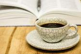φλιτζάνι καφέ και άνοιξε βιβλίο με στυλό στο τραπέζι ξύλινο — Φωτογραφία Αρχείου