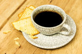 Cup of coffee with crackers on wood table. — Stock Photo