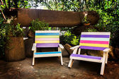 Colorful wooden lawn chairs in the spring garden. — Stockfoto